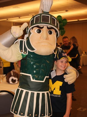 Sparty and Wolverine fan Bella Restauri enjoy friendly competition at a 2014 fundraiser for VINA Community Dental Center.