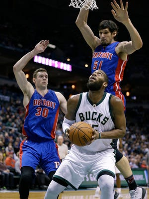 Bucks' Greg Monroe drives to the basket against Pistons' Jon Leuer, left, and Boban Marjanovic during the second half.