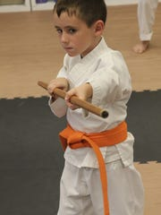 Double gold medal winner at the recent national championships, Dominic Scarpa, 5, demonstrates a move in kobudo (weapons discipline).