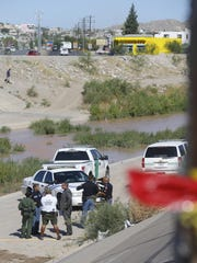 El Paso police officers and U.S. Border Patrol agents survey the area where the body of a 17-year-old boy was pulled from the Rio Grande on Tuesday.