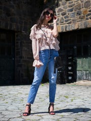 Christine Donnelly wears a light pink one-shoulder ruffle top by Zara; high-waisted jeans from Anthropologie; and black studded sandals by Sol Sana.
