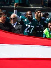 Eagles' Malcolm Jenkins, 27, raises his fist next to Philadelphia Eagles owner Jeffrey Lurie during the national anthem before the start of their home season opener against the New York Giants Sunday at Lincoln Financial Field.