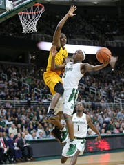 Michigan State's Cassius Winston drives to the basket and draws foul from Long Beach State's Jordan Griffin during MSU's 102-60 win on Thursday, Dec. 21, 2017, at Breslin Center.