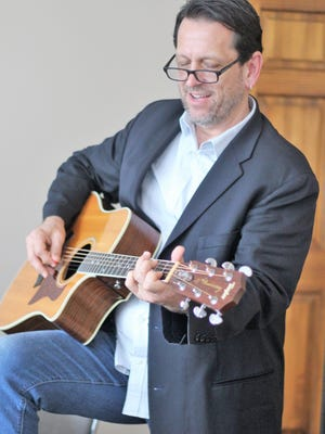 Randy Bishop strums his guitar Thursday afternoon. A resident of Florida, he is back in town for a show at the Owen's Opera House on Saturday.