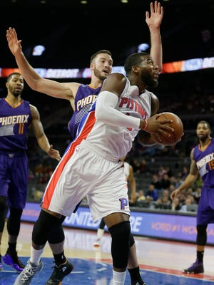 Detroit Pistons forward Greg Monroe (10) is defended by Phoenix Suns center Miles Plumlee during the first half of an NBA basketball game in Auburn Hills, Mich., Wednesday, Nov. 19, 2014.