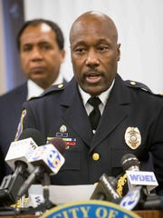 Wilmington Mayor Dennis Williams in the background as police chief Bobby Cummings answers questions at a press conference.