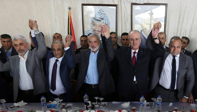 In this Oct. 2, 2017, file photo provided by Prime Minister Office, from left in front row, Hamas leader in the Gaza Strip Yahya Sinwar, Head of Palestinian General Intelligence Majid Faraj, Head of the Hamas political bureau Ismail Haniyeh, Palestinian Prime Minister Rami Hamdallah and an Egyptian mediator hold their hands up during a meeting in Gaza City. The leader of Hamas said on Thursday, Oct. 12, 2017 that his group has reached an agreement with the rival Fatah party of Palestinian President Mahmoud Abbas after Egyptian-brokered talks about the terms of control of the Gaza Strip.