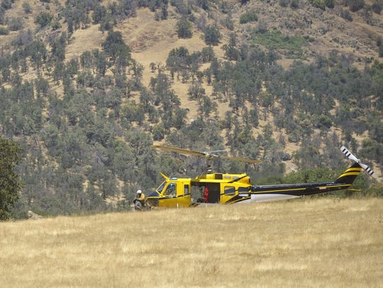 Fire crews pack up a helicopter during the King Fire