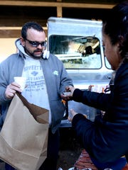 Ray Martin, 47, of Salem, accepts a chocolate dessert from a volunteer during the Feed the Need event under the Marion Street Bridge in Salem on Thursday, Nov. 26, 2015. Local food trucks and other volunteers gave full to-go Thanksgiving meals for 150 people.