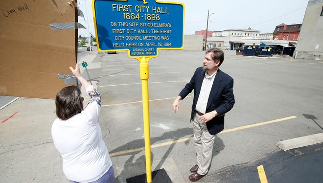 Bruce Whitmarsh, Chemung County Historical Society director, and Elmira councilwoman Nanette Moss unveil the new historical marker of the former city hall site, located behind the sign, on Saturday.
