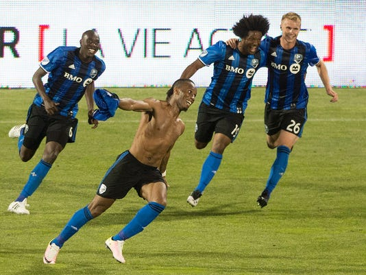 Montreal Impact's Didier Drogba, foreground, celebrates with teammates Hassoun Camara (6) Michael Salazar (19) and Kyle Fisher (26) after scoring the winning goal against the Los Angeles Galaxy during second-half MLS soccer game action in Montreal, Saturday, May 28, 2016. (Graham Hughes/The Canadian Press via AP) MANDATORY CREDIT