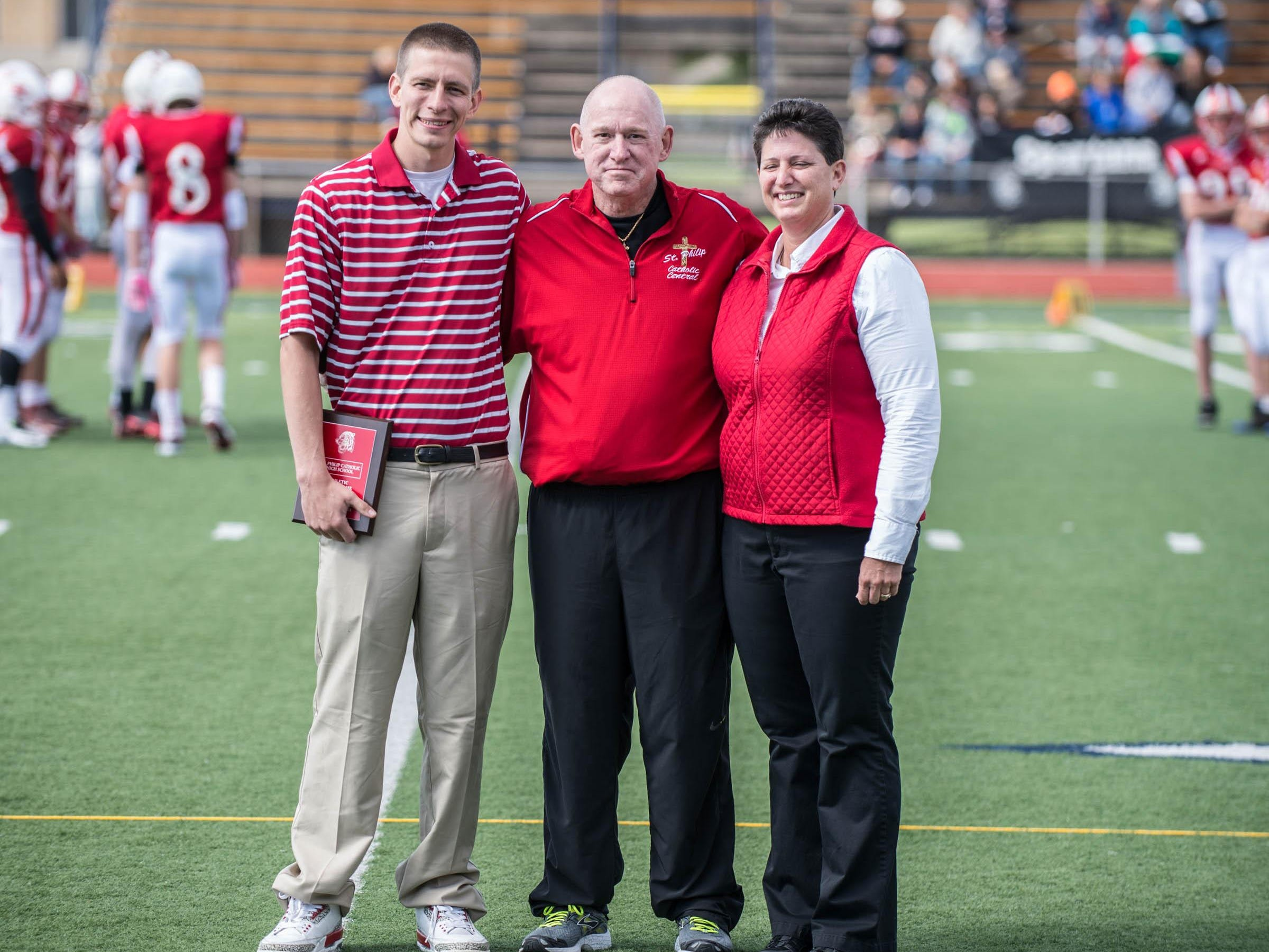 Mike Leifeld (left) and Ted Fitzgerald are joined by Athletic Director/Principal Vicky Groat after each were inducted into St. Philip's Athletic Hall of Fame during Saturday's Homecoming game.