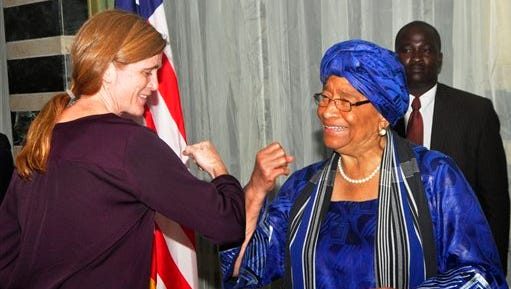 FILE- In this Tuesday, Oct. 28, 2014, file photo, Liberia President Ellen Johnson Sirleaf, right, gives American ambassador to the United Nations Samantha Power, left, what is know as the 'Ebola hand shake' during a press conference in the city of  Monrovia, Liberia. Liberia is now free of Ebola after going 42 days — twice the maximum incubation period for the deadly disease — without any new cases, the World Health Organization announced on Saturday, May 9, 2015. President Ellen Johnson Sirleaf toured health centers in Monrovia on Saturday, embracing and taking group photos with health workers. She was accompanied by U.S. Ambassador Deborah Malac. (AP Photo/ Abbas Dulleh, File)