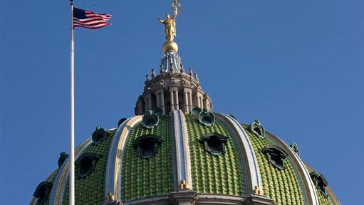 The United States flag waves in the wind at the Pennsylvania Capitol building Tuesday, Dec. 8, 2015, in Harrisburg, Pa. The Pennsylvania House and Senate moved toward a showdown over competing spending and tax plans Monday, with the fate of suffering counties, schools and social services agencies hanging in the balance of a 5-month budget stalemate.