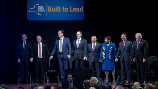 From left, Attorney General Eric Schneiderman, Comptroller Thomas DiNapoli, Senate Majority Leader John Flanagan, New York Gov. Andrew Cuomo, Assembly Speaker Carl Heastie, Senate Democratic Conference Leader Andrea Stewart-Cousins, Independent Democratic Conference Leader Jeff Klein, and Assembly Minority Leader Brian Kolb hold hands before Cuomo's State of the State address and executive budget proposal at the Empire State Plaza Convention Center on Wednesday, Jan. 13, 2016, in Albany, N.Y.