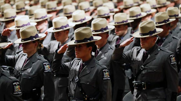 Graduating New York State Police salute during a ceremony at the Empire State Plaza Convention Center on Thursday, Oct. 13, 2016, in Albany, N.Y. The 204th basic school session graduated about 200 new troopers.