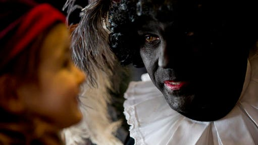 "In this Friday Dec. 5, 2014 file photo three-and-a-half-year-old Ita Krans, left, talks to Black Pete, the black-faced sidekick of Sinterklaas, the Dutch version of Santa Claus, during a short ceremony at the mayor's office in Amsterdam, Netherlands. The steam boat carrying Sinterklaas is not due to chug into the historic harbor of Maassluis until next weekend, but the annual polarized debate about his helper ""Black Pete"" has been underway for weeks."