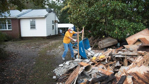 Allen Kent, with Southern Baptist Convention Disaster Relief, throws wood onto a pile that was removed from the home of Bill Jones and was heavily damaged by floodwaters caused by rain from Hurricane Matthew in Nichols, S.C., Thursday, Oct. 27, 2016. Nearly a month since floodwaters consumed the town, few have returned. The fear is that many never will. A stew of contaminants stood inches to feet deep in homes for a week. As it receded, toxic black mold grew rampant, leaving nearly all of the town's 261 homes uninhabitable. Few, if any, had flood insurance.