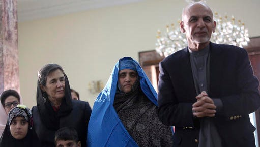 """Afghan President Ashraf Ghani, right, meets with National Geographic's famed green-eyed """"Afghan Girl"""" Sharbat Gulla at the Presidential palace in Kabul, Afghanistan, Nov. 9, 2016. Afghanistan's president on Wednesday welcomed home Gulla who was deported from Pakistan after a court had convicted her on charges of carrying a forged Pakistani ID card and staying in the country illegally."""