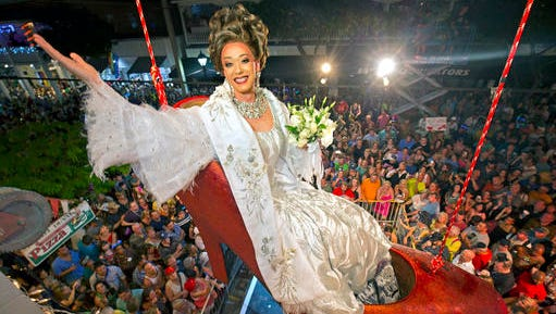FILE - In this Thursday, Dec. 31, 2015, file photo, provided by the Florida Keys News Bureau, female impersonator Gary Marion, known as Sushi, hangs in a giant replica of a woman's high heel shoe in Key West, Fla. Beginning at about 11:59 p.m. Thursday, the shoe with Sushi in it is to be lowered to Duval Street to mark the beginning of 2016. The Big Red Shoe Drop is one of several of the subtropical island city's takeoffs on New York City's Times Square ball drop.