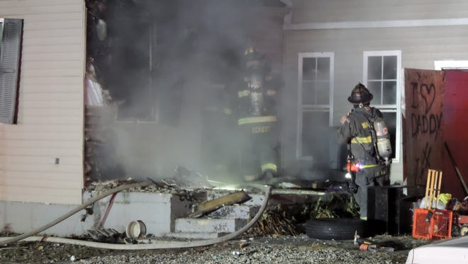 Wayne Township firefighters are shown extinguishing a fire early Thursday, Jan. 1, 2015, at a home at at 4120 W. Vermont St. A 25-year-old man had been rescued from the home by three Indianapolis police officers, before firefighters arrived at the scene.
