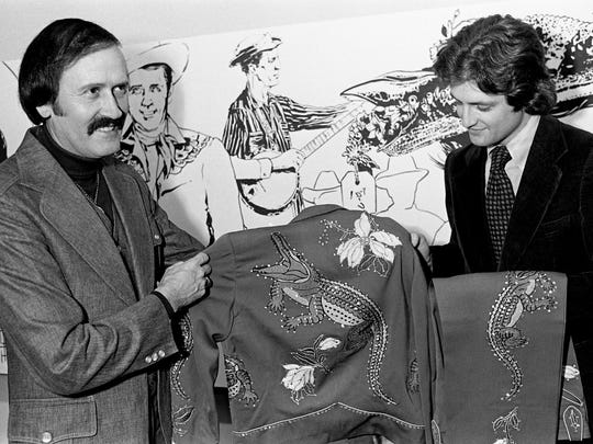 "Country music star Jimmie C. Newman, left, joins the ranks of entertainers contributing to the Country Music Hall of Fame costume collection on March 2, 1978, when he donated one of his early costumes. Accepting the costume designed by ""Nudie"" is Hall of Fame education curator Kyle Young."
