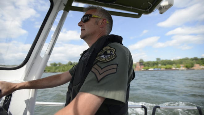 Vermont State Police Cpl. Kevin Mays of the Marine Division drives his boat on Lake Champlain in Burlington on Thursday. Mays' boat was one of four patrolling Vermont shorelines as the search continues for two escaped New York prison inmates.