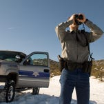Published caption: PHOTOS BY PATRICK CUMMINGS/RENO GAZETTE-JOURNAL While patrolling the Peavine Mountain area Friday, Nevada Department of Wildlife Game Warden Randy Lusetti uses binoculars to scan the area for hunters. ooo  While patrolling the Peavine Mountain area, Nevada Department of Wildlife Game Warden Randy Lusetti uses binoculars to scan the area for hunting activity on December 14, 2007.