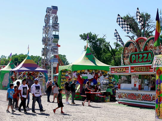 Visitors stroll through the carnival during Aztec Fiesta