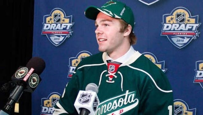 After donning a Minnesota Wild cap and jersey, Nick Boka proudly stands at the podium after being drafted by the NHL team.