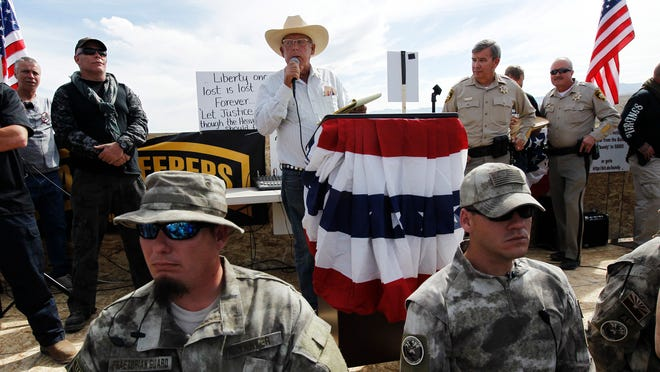 Rancher Cliven Bundy, middle, addresses his supporters with Clark County Sheriff Doug Gillespie, right, on April 12, 2014.
