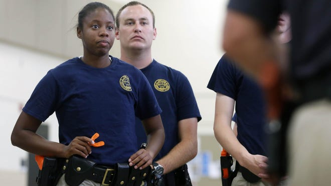 Sadé Pointer with the Dubuque Police Department looks on Tuesday, Sept. 29, 2015 as instructors lead her class through a demonstration at the Iowa Law Enforcement Academy in Johnston.