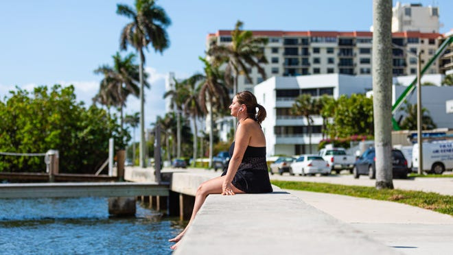 Kayla Lawhead of West Palm Beach sits on the seawall getting some sun on S. Flagler Drive in West Palm Beach.