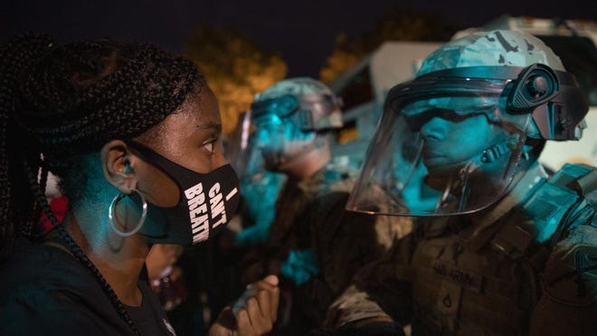 A demonstrator calls out to a military line near the White House to protest the death of George Floyd, Wednesday, June 3, 2020, in Washington. Floyd died after being restrained by Minneapolis police officers.