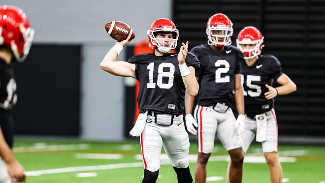 Georgia quarterback JT Daniels (18), D'Wan Mathis (2) and Carson Beck (15) during the Bulldogs' practice session in Athens, Ga., on Wednesday, Oct. 14, 2020.