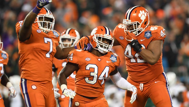 Clemson linebacker Kendall Joseph (34) celebrates with defensive lineman Austin Bryant (7), left, and defensive lineman Christian Wilkins (42) after intercepting a Miami pass during the 3rd quarter of the ACC championship game against Miami at Bank of America Stadium in Charlotte on Saturday, December 2, 2017.