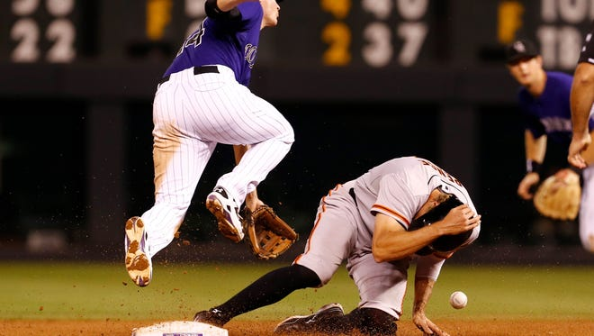 San Francisco Giants right fielder Hunter Pence (8) steals second against Colorado Rockies short stop Josh Rutledge (14) in the eighth inning at Coors Field.