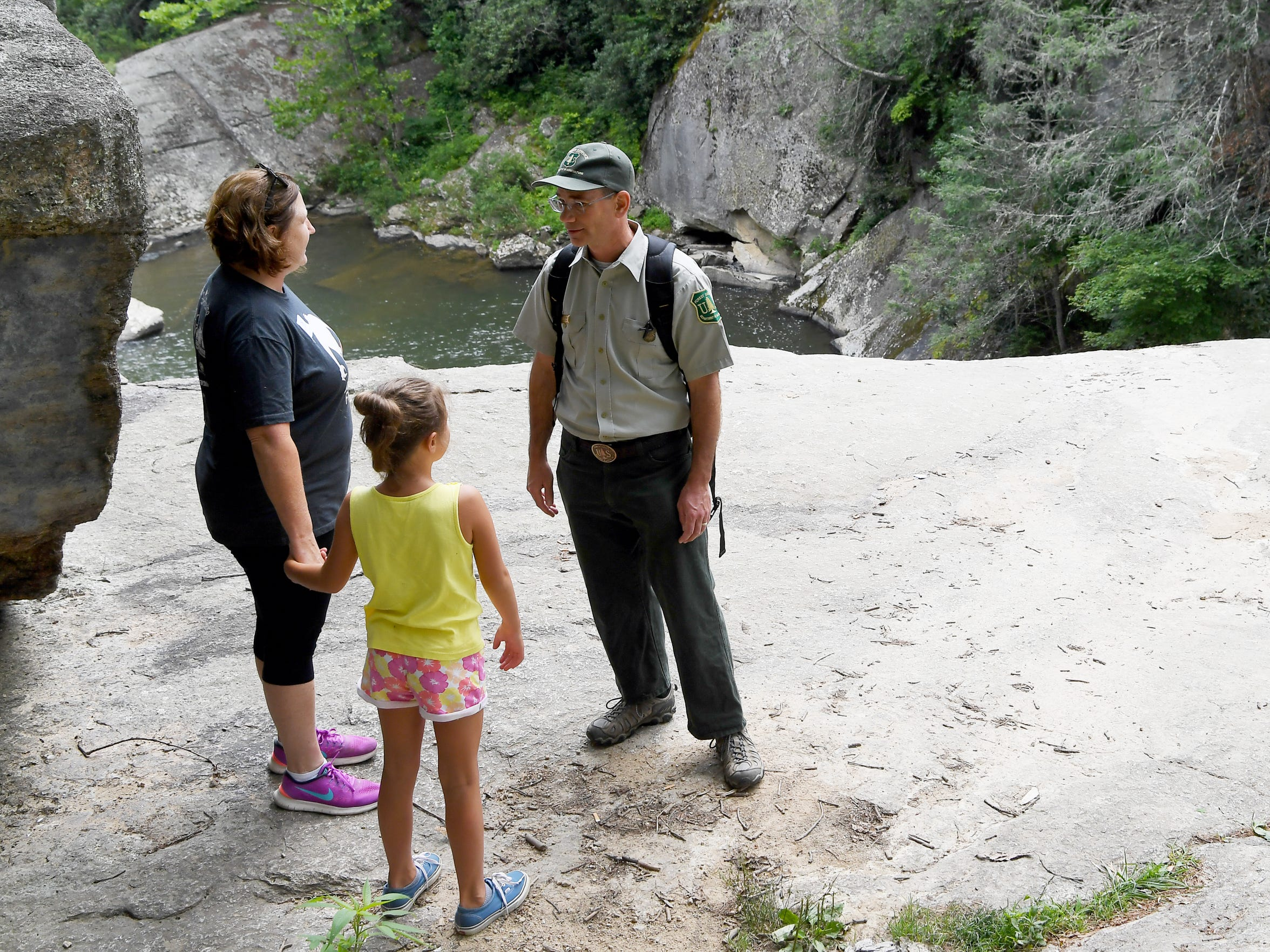 Richard Thornburgh, Appalachian District Ranger with the US Forest Service, talks with Dell Lowe and her daughter Ali, 8, at the top of Elk River Falls July 20, 2018.