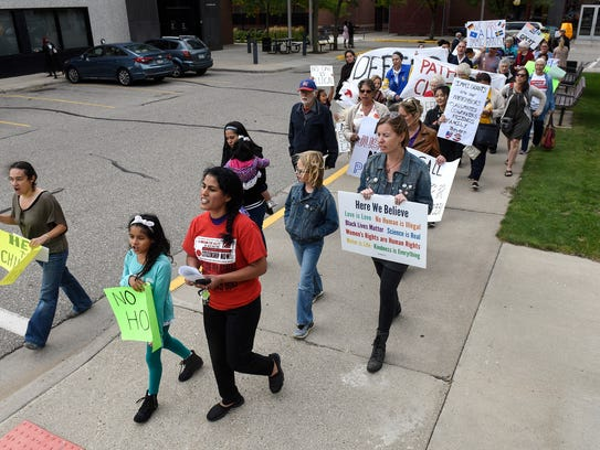 People march around the Stearns County Courthouse Tuesday,