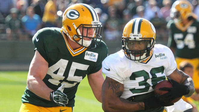 Green Bay Packers running back LaDarius Perkins grabs a pass in front of linebacker Jake Doughty during training camp practice Wednesday at Ray Nitschke Field.