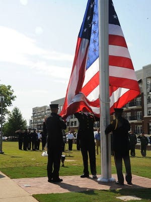 Members of Maxwell Air Force Base's Honor Guard raise the American Flag Tuesday on Maxwell Boulevard.