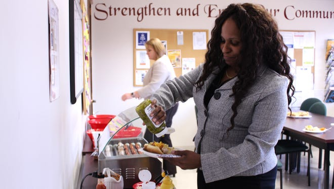Sheila Foxx, an application support analyst at Sage Rutty & Co. Inc. grabs a hot dog at a lunch prepared for employees by Sage Rutty President and Chairman Wayne Holly.