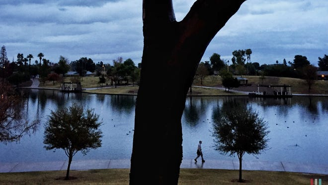 After a night of rain, a walker enjoys a cool morning walk at Tempe's Kiwanis Park on Dec. 22, 2016.