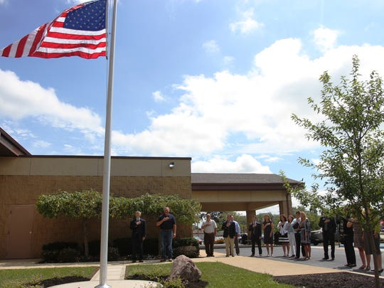 COTC officials and members of the Pataskala campus advisory board say the Pledge of Allegiance during a ceremony celebrating the placement of a new flagpole at the campus.