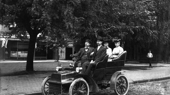 Area residents pose in an open-top car on North Broad Street in the early 1900s.