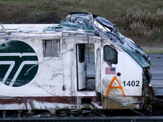 The engine from an Amtrak train crash onto Interstate 5 two days earlier sits before being transported away from the scene Wednesday.