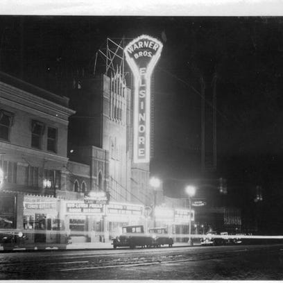 The Elsinore Theatre is seen in the 1930s, with cars and bicycles in front. Willamette Heritage Center / P 1998.008.0012