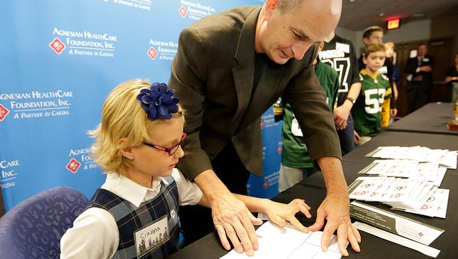 Sianna Feucht, a second-grader at St. Mary's Springs Academy in Fond du Lac, receives help from Kenny Hansmire, who takes her finger print for inclusion in her child ID kit.