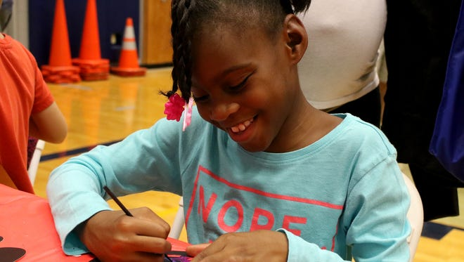 Naziah Mallett creates her own ornament at the crafts table during the Wichita Falls Parks and Recreation Christmas in Scotland Park Saturday, Dec. 2, 2017, at Scotland Park Elementary School. Kids and their families met Mr. and Mrs. Claus, rode a train and played various carnival games.