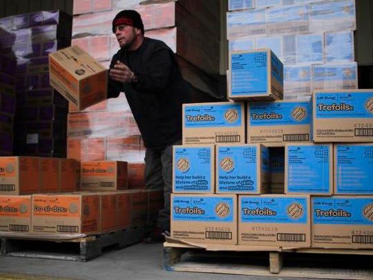 Volunteer Robert Morgan tosses a box of Girl Scout